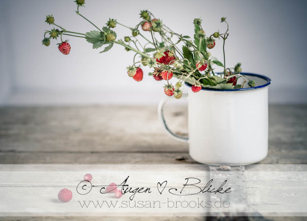 Bouquet of wild strawberries  in enamel cup on old wooden door
