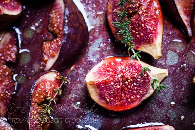 Roasted figs on baking tray, with balsamic vinegar, olive oil, and grape juice, close-up